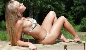 Fascinating youthful female with pretty tits lies on an outdoor bench sunbathing