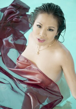 Exotic dame from Asia not shy to swim absolutely undressed in private pool